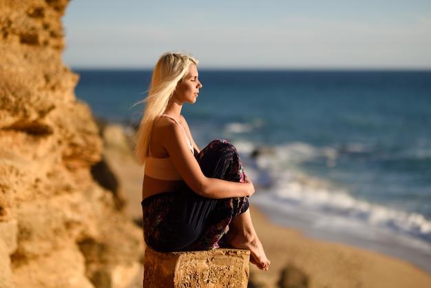 Frau, die den sonnenuntergang an einem schönen strand genießt