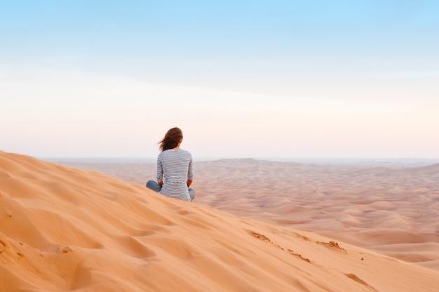 Frau, die den sonnenuntergang im wüstensand aufpasst
