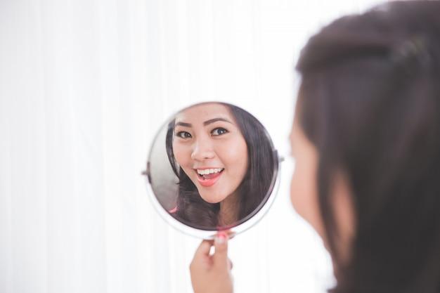 Frau, die den spiegel betrachtet