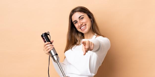 Frau, die den stabmixer über der isolierten wand verwendet, die vorne mit glücklichem ausdruck zeigt