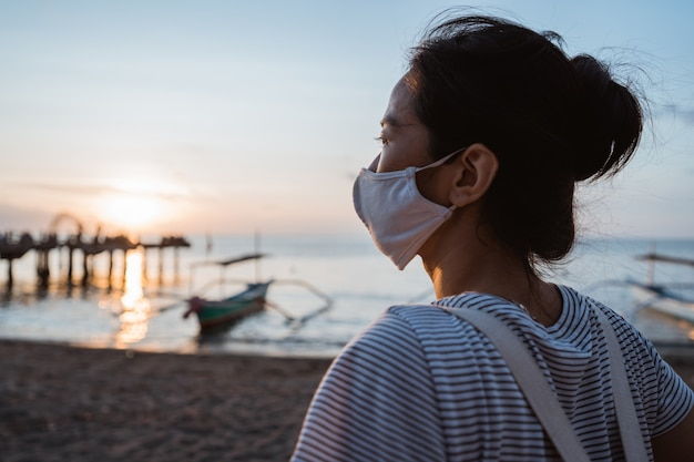 Frau, die den strand mit gesichtsmaske für gesund am sonnigen morgen besucht