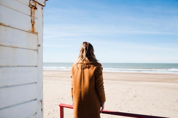 Frau, die den strand vom hausponton bewundert
