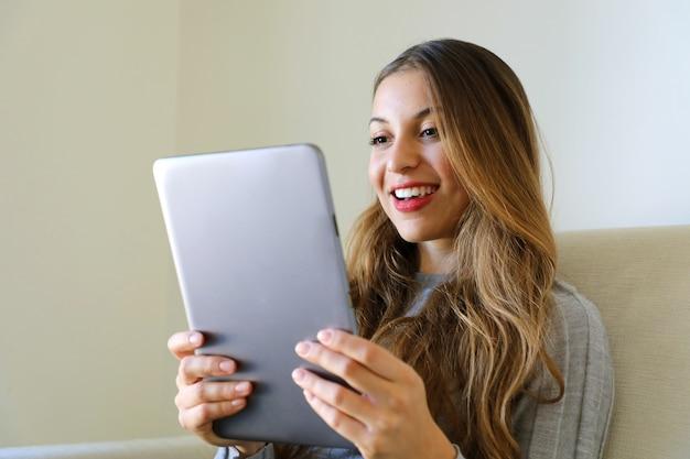 Frau, die den tablet-pc-computer betrachtet, der zu hause sitzt