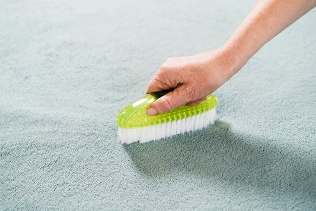 Frau, die den teppich bürstet