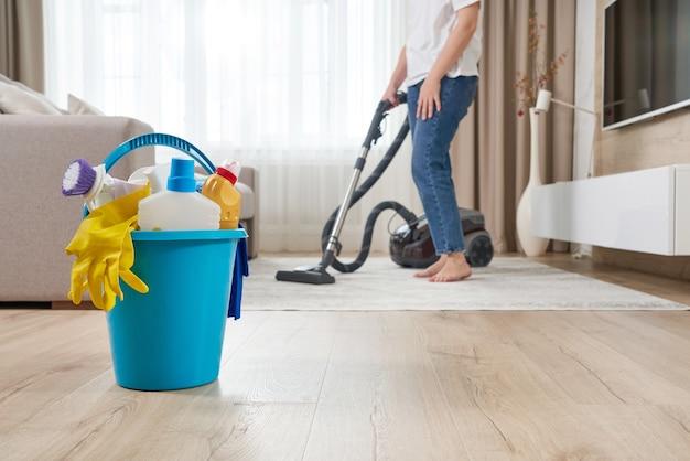 Frau, die den teppich mit staubsauger im wohnzimmer reinigt