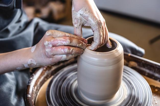 Frau, die den ton mit ihren händen bildet, die krug in einer werkstatt schaffen
