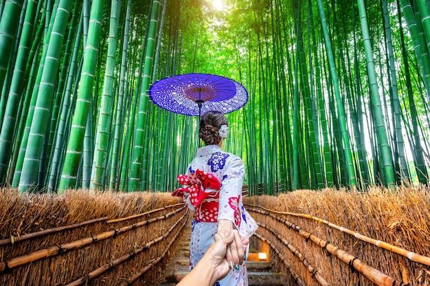 Frau, die den traditionellen japanischen kimono trägt, der die hand des mannes hält und ihn zum bambuswald in kyoto, japan führt.