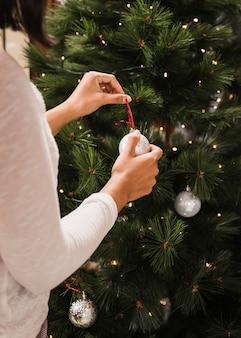 Frau, die den weihnachtsbaum mit weißen bällen verziert