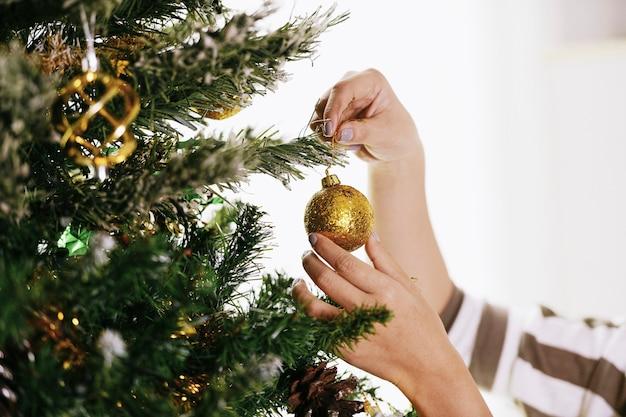 Frau, die den weihnachtsbaum schmückt.