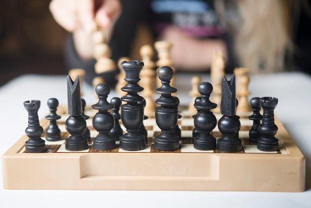 Frau, die denkt, wie man schachkonzept-geschäftsstrategie für gewinn spielt
