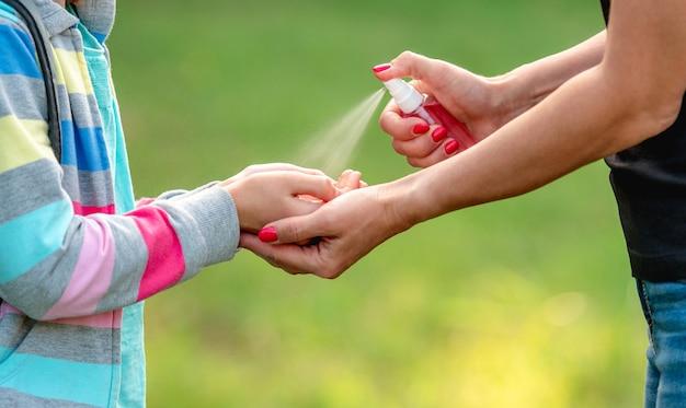 Frau, die desinfektionsmittel auf mädchenhänden draußen, nahaufnahmeansicht verbreitet