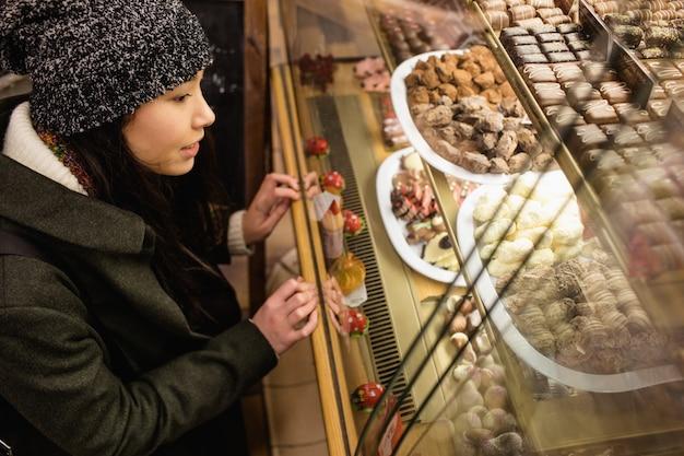 Frau, die desserts am dessertzähler betrachtet