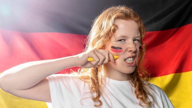 Frau, die deutsche flagge auf ihrem gesicht malt