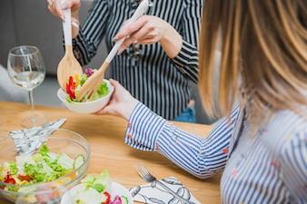 Frau, die Diätlebensmittel in Platte einsetzt