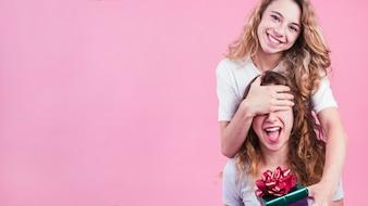 Frau, die die Augen ihres Freunds gibt Geschenkbox gegen rosa Hintergrund bedeckt