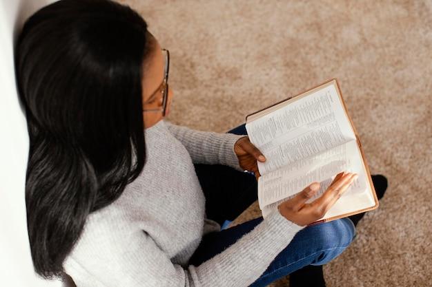 Frau, die die bibel drinnen liest