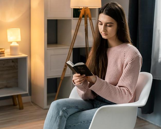 Frau, die die bibel liest, während sie im stuhl sitzt