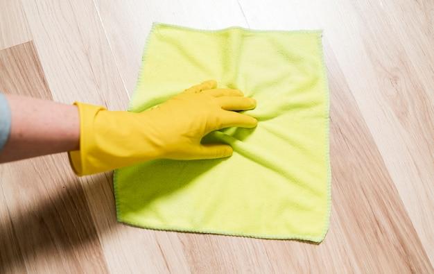 Frau, die die böden mit lappen reinigt