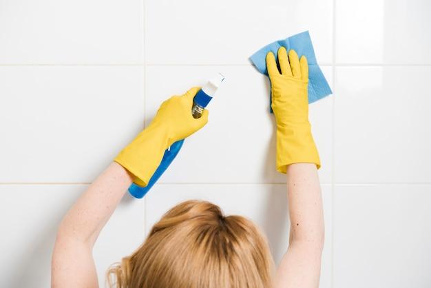 Frau, die die duschwand reinigt