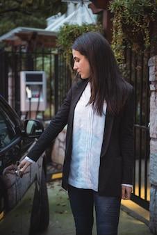 Frau, die die elektrische autotür an der ladestation des elektrofahrzeugs öffnet