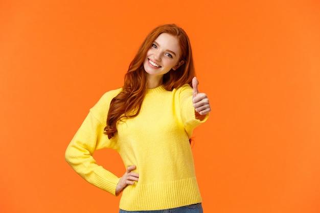 Frau, die die erlaubnis gibt, sag ja. fröhliche rothaarige frau im gelben pullover strecken den arm aus