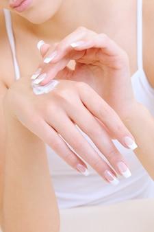 Frau, die die feuchtigkeitsspendende kosmetische creme auf händen anwendet