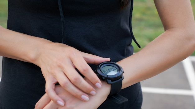 Frau, die die fitness-smartwatch zum laufen einrichtet. sportliches mädchen, das uhrengerät überprüft, nahaufnahme