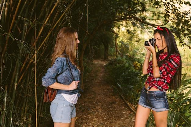 Frau, die die fotografie ihres freunds mit kamera im wald anklickt