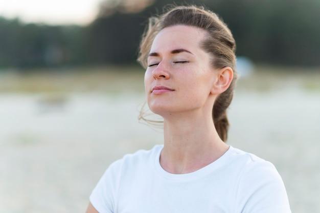 Frau, die die frische ozeanbrise am strand während des trainings aufnimmt
