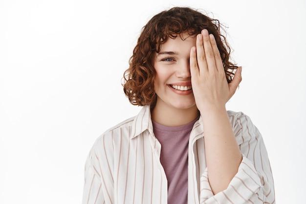 Frau, die die hälfte des gesichts mit der handfläche hält, glücklich lächelt, die sicht im optikergeschäft überprüft oder vor und nach dem effekt zeigt, auf weiß steht