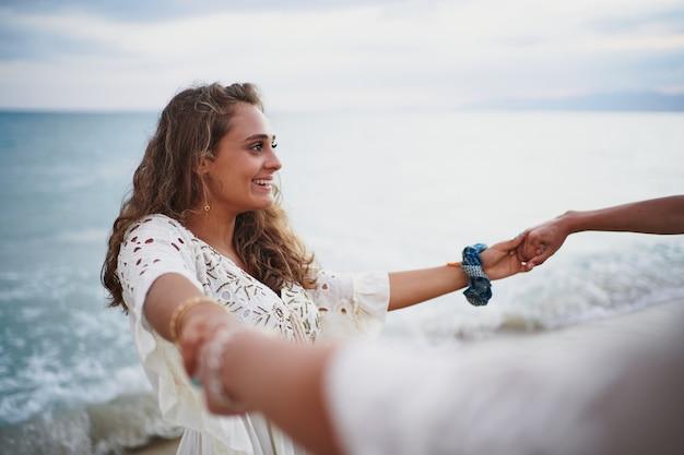 Frau, die die hände ihrer freundin packt, einen kreis bildet und sich am strand dreht