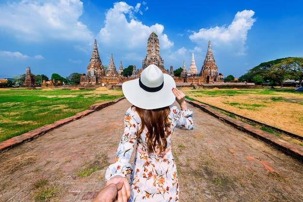 Frau, die die hand des mannes hält und ihn zum ayutthaya historischen park, wat chaiwatthanaram buddhistischer tempel in thailand führt.