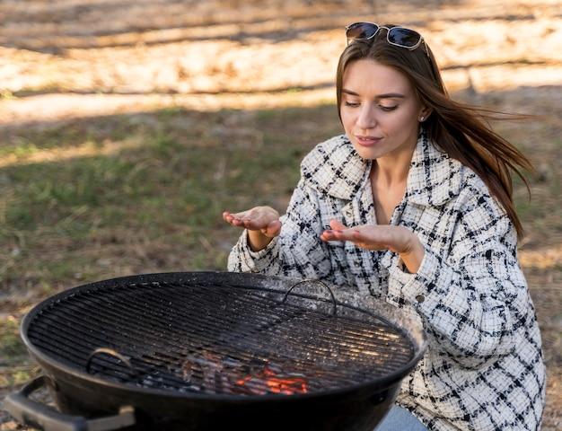 Frau, die die hitze des grills im freien testet