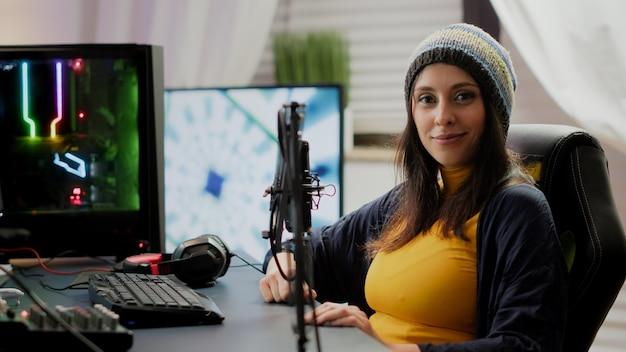 Frau, die die kamera betrachtet, die vor einem leistungsstarken rgb-computer sitzt und ein online-weltraum-shooter-videospiel-streaming-spiel im internet spielt. pro cyber-videospieler, der spiele im gaming-heimstudio spielt