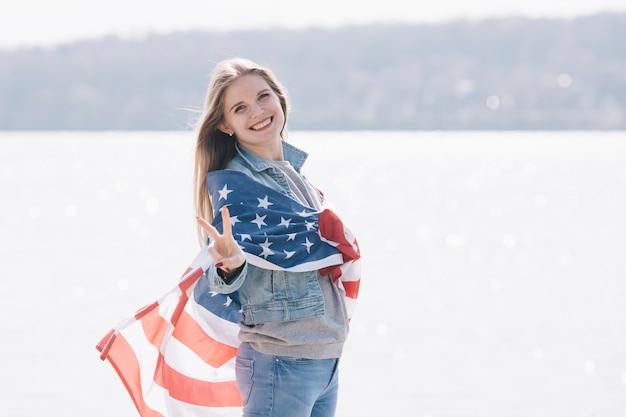 Frau, die die kamera eingewickelt in der amerikanischen flagge lächelt und betrachtet