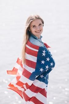Frau, die die kamera eingewickelt in wellenartig bewegender amerikanischer flagge lächelt und betrachtet