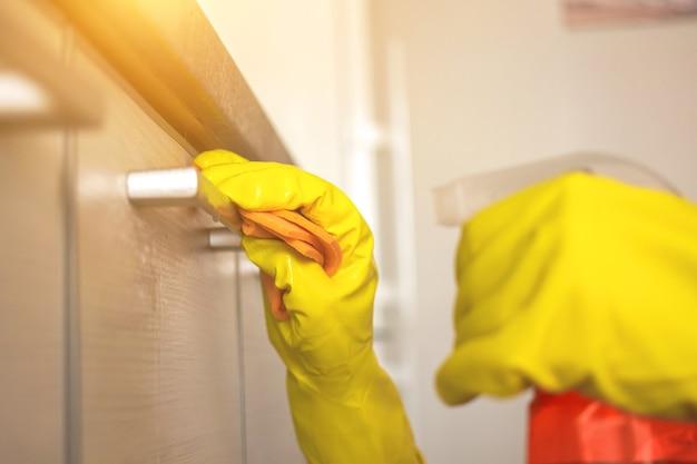 Frau, die die küche und den küchenschrank in gelbem gummihandschuh und spültuch mit sprühflasche in nahaufnahme säubert