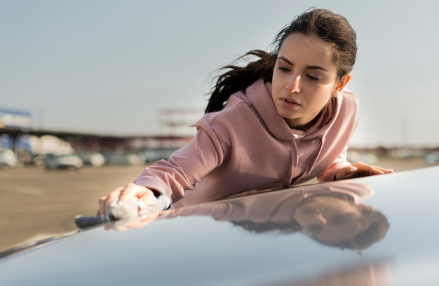 Frau, die die motorhaube des autos reinigt