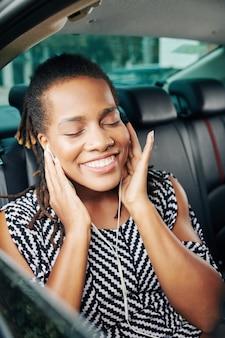 Frau, die die musik im auto genießt