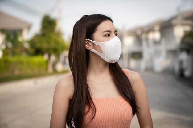 Frau, die die n95 atemschutz-gesichtsmaske trägt, schützt verschmutzung (pm2.5), smog und viren.