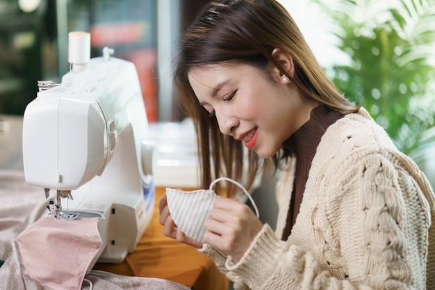 Frau, die die nähmaschine verwendet, um die gesichtsmaske während der coronavirus-pandämie zu nähen