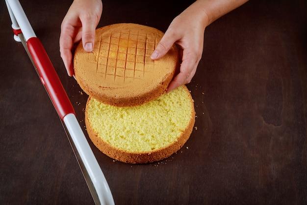 Frau, die die oberseite des kuchens mit einem gezackten richtkuchen schneidet. eine torte backen.