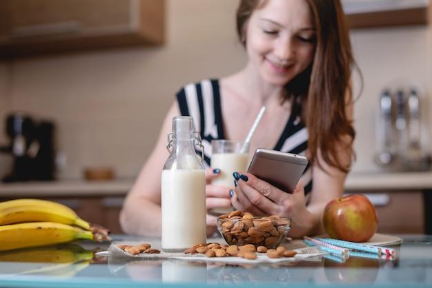 Frau, die die organische mandelmilch hält ein telefon in ihrer hand in der küche trinkt. gesundes vegetarisches produkt