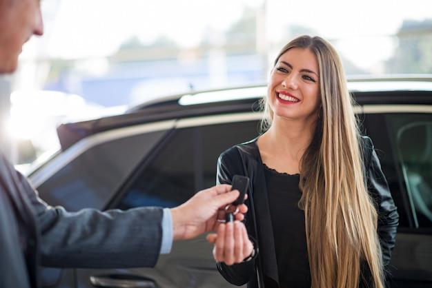 Frau, die die schlüssel für ihr auto in einem ausstellungsraum nimmt