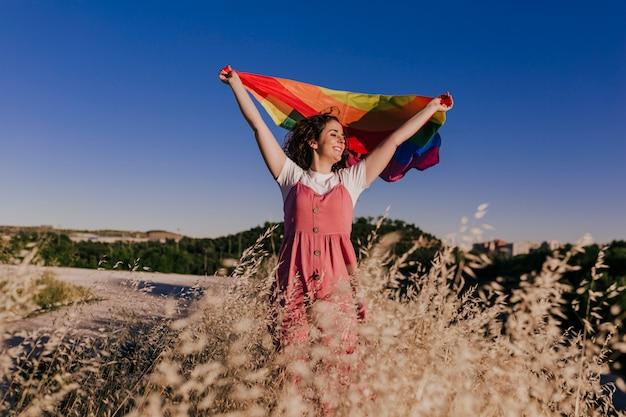 Frau, die die schwule regenbogenfahne bei sonnenuntergang hält. glück, freiheit und liebeskonzept für gleichgeschlechtliche paare. lebensstil im freien
