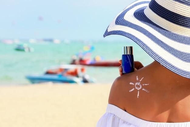 Frau, die die sonnencremeflaschencreme in der hand hält, mit sonnencreme-lotionscreme, die auf ihren rücken aufgetragen wird und zeichnet, ist die sonne.