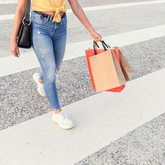 Frau, die die straße mit einkaufstüten überquert