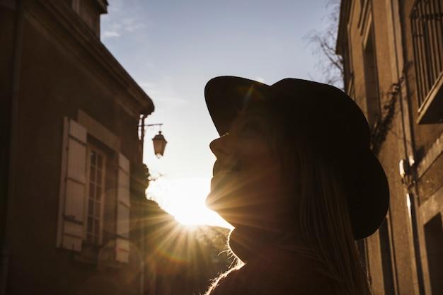 Frau, die die straßen von angers, frankreich bei sonnenuntergang besichtigt