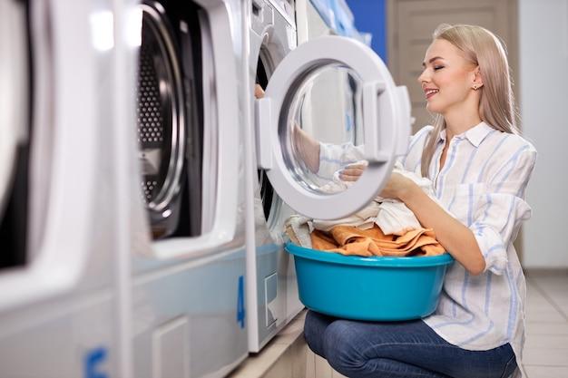 Frau, die die täglichen aufgaben erledigt - wäsche. weibliche gefaltete saubere kleidung im wäschebecken, seitenansicht auf frau, die den prozess des reinigens im waschhaus genießt. reinigungs-, waschkonzept