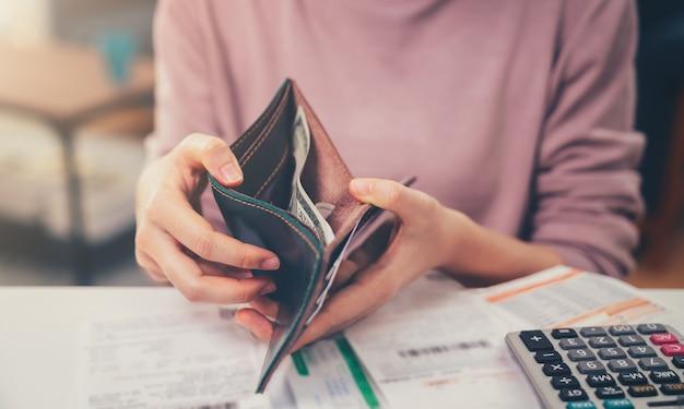 Frau, die die taschengeldbörse hält und mit geld, kreditkarte und spesenrechnung und berechnung über schuldenrechnungen monatlich am tisch im haus öffnet.